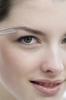 Thumbnail Woman plucking her eyebrow, close up (studio)