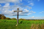 Thumbnail large metal cross which guards an oilseed rape field