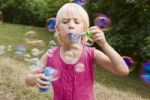 Thumbnail Blond 7 year old girl blowing bubbles