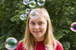 Thumbnail Thirteen year old girl amidst bubbles