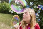 Thumbnail Thirteen year old girl blowing bubbles