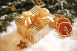 Thumbnail Christmas present with branches of fir, dried orange slices and decorations on snow