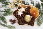 Thumbnail Christmas plate with star anise, cinnamon stars, a golden Christmas tree bauble and dried orange slices on branches of fir and snow