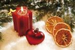 Thumbnail Lit star-shaped candle with a heart-shaped Christmas tree bauble, branches of fir, dried orange slices and decorations on snow