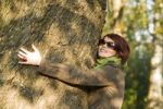 Thumbnail Young woman embracing a tree trunk in autumn