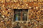 Thumbnail Window of a house framed by the winter stock of firewood.