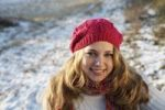 Thumbnail Laughing teenage girl wearing a hat and gloves, sitting in a wintery landscape