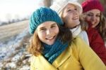 Thumbnail Smiling teenage girls wearing hats, sitting in a wintery landscape