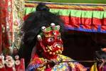 Thumbnail Monk wears fearful and red mask of a demon at festival in colourful decorated Rongbuk Monastery Tibet China