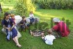 Thumbnail familiy having a barbecue at an open fire place campfire