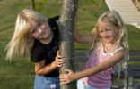 Thumbnail Two blonde girls next to a tree trunk