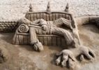 Thumbnail Sand sculpture of a tramp with a dog lying on a bench