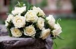 Thumbnail Bridal bouquet with white roses on the edge of a fountain