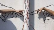 Thumbnail Finger pointing to a wall graffiti