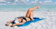 Thumbnail Girl with hat on a white sandy beach with turquoise sea lying on a blue towel