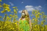 Thumbnail Blond girl wearing a face mask while standing in a field of rape