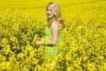 Thumbnail Blond girl smiling while standing in a field of rape