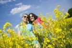 Thumbnail Two girls wearing sunglasses and smiling while standing in a field of rape