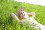 Thumbnail Portrait of a smiling blond girl wearing a sun hat while lying on a meadow