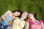 Thumbnail Three smiling girls lying in the grass, smiling