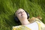 Thumbnail Portrait of a sleeping blond girl lying in the grass wearing headphones