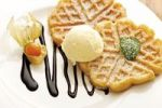 Thumbnail Waffles on a plate with physalis, nougat cream and a scoop of vanilla ice cream