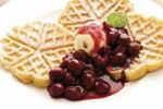 Thumbnail Waffles on a plate with sour cherries and a scoop of vanilla ice cream
