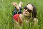 Thumbnail Young woman, 30, relaxed, lying on a lawn in spring