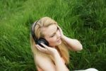 Thumbnail Young blonde woman sitting on a lawn, listening to music with headphones