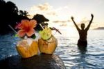 Thumbnail Two coconuts with cocktails and decorations on a granite rock at sunset, in the back a woman is standing in the sea, Seychelles, Indian Ocean, Africa