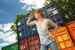 Thumbnail Young woman standing in front of a container, looking into the distance