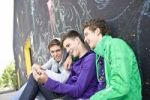 Thumbnail Three boys sitting with their backs against a wall, sending text messages, cool