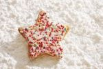 Thumbnail Star-shaped short pastry cookies, covered with colourful sugar pearls, on icing sugar