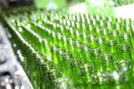 Thumbnail Rows of empty green glass beer bottles on a brewery conveyor
