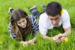 Thumbnail Young couple, students, lying on a spring meadow and talking with each other, France, Europe