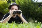 Thumbnail Young man with binoculars in a meadow