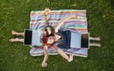 Thumbnail Two young women with laptops sit on a blanket in a meadow