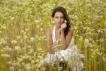 Thumbnail Young woman in a white dress in a field of chamomile flowers