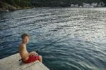 Thumbnail Boy, 13, seated while fishing on a pier, Bay of Valun, Cres Island, Croatia, Europe