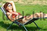 Thumbnail young woman basks in a canvas chair