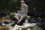 Thumbnail Male, mid 40s, sitting in a stream and reading a book, Hoellbach, Black Forest, Germany, Europe