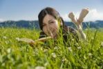 Thumbnail Woman with book lying in a meadow