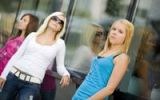 Thumbnail Three teenage girls leaning against a window-front