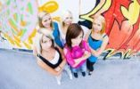 Thumbnail Group of teenage girls in front of a graffiti wall