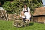 Thumbnail Two young women wearing Dirndl dresses with a wheelbarrow