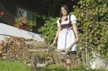 Thumbnail Young peasant woman wearing a Dirndl dress with a wheelbarrow