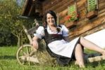 Thumbnail Young woman wearing a Dirndl dress sitting on a wheelbarrow on a farm
