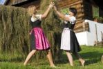 Thumbnail Two young woman wearing Dirndl dresses harvesting hay