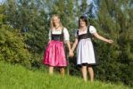 Thumbnail Two young women wearing Dirndl dresses walking hand in hand over a meadow
