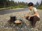 Thumbnail Young woman cooking, frying chicken stir fry on a camp fire, gravel bar, upper Liard River, Yukon Territory, Canada
